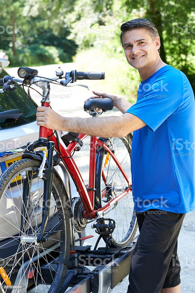 Mature Male Cyclist Taking Mountain Bike From Rack On Car stock photo