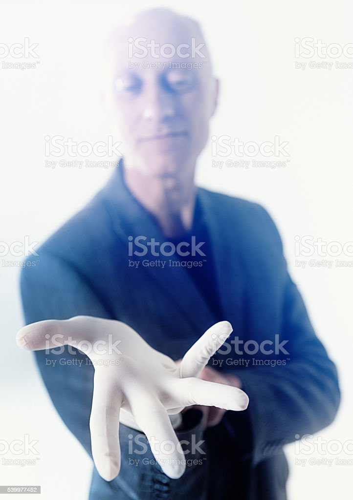 Mature male doctor donning surgical glove, preparing for medical examination stock photo