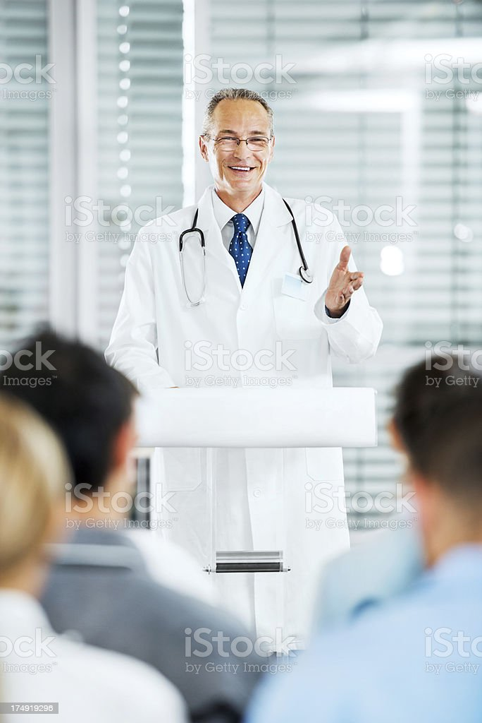 Mature male doctor giving a speech on seminar. royalty-free stock photo