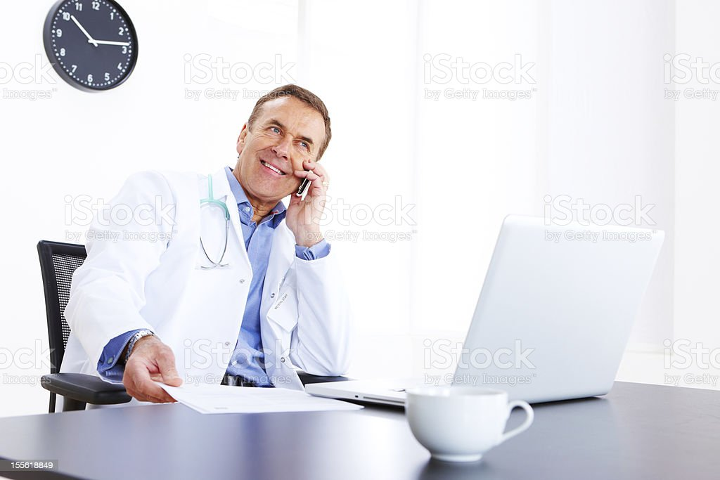 Mature male doctor sitting at desk in office royalty-free stock photo