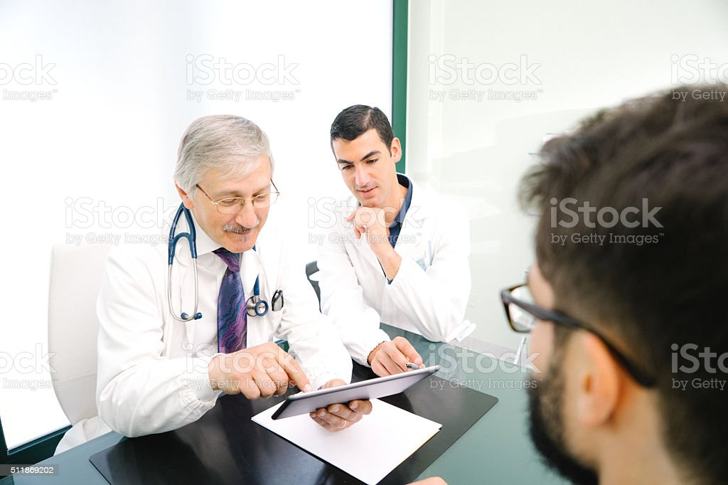 Mature Male Doctor Using A Digital Tablet For His Diagnosis. stock photo