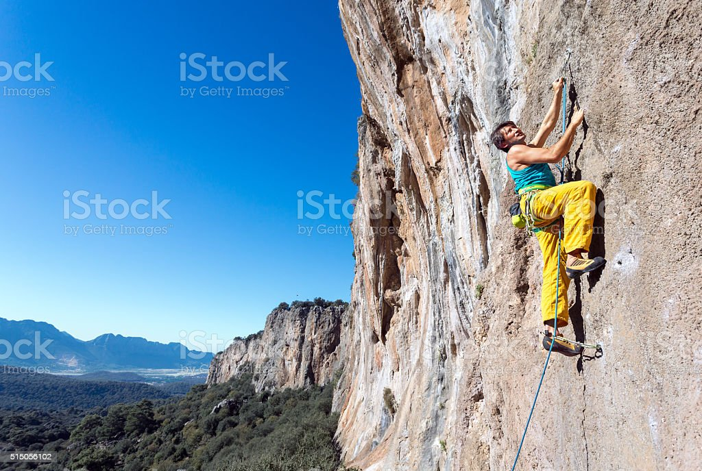 Mature male extreme Climber moving up on rocky Wall stock photo