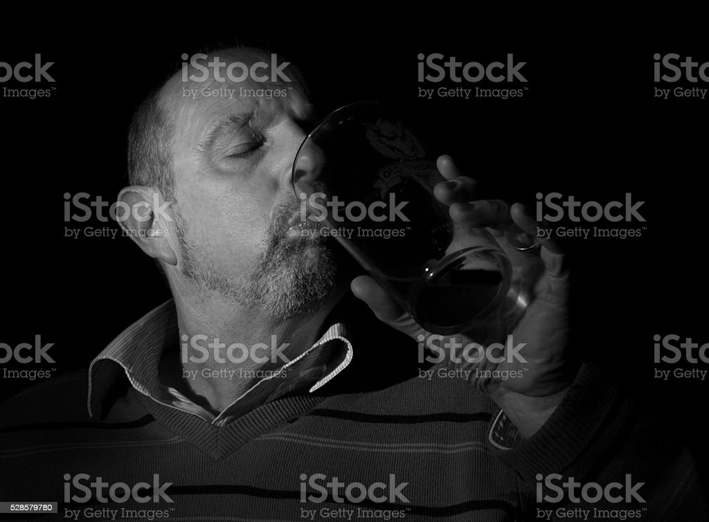 mature male having a beer with black back round stock photo