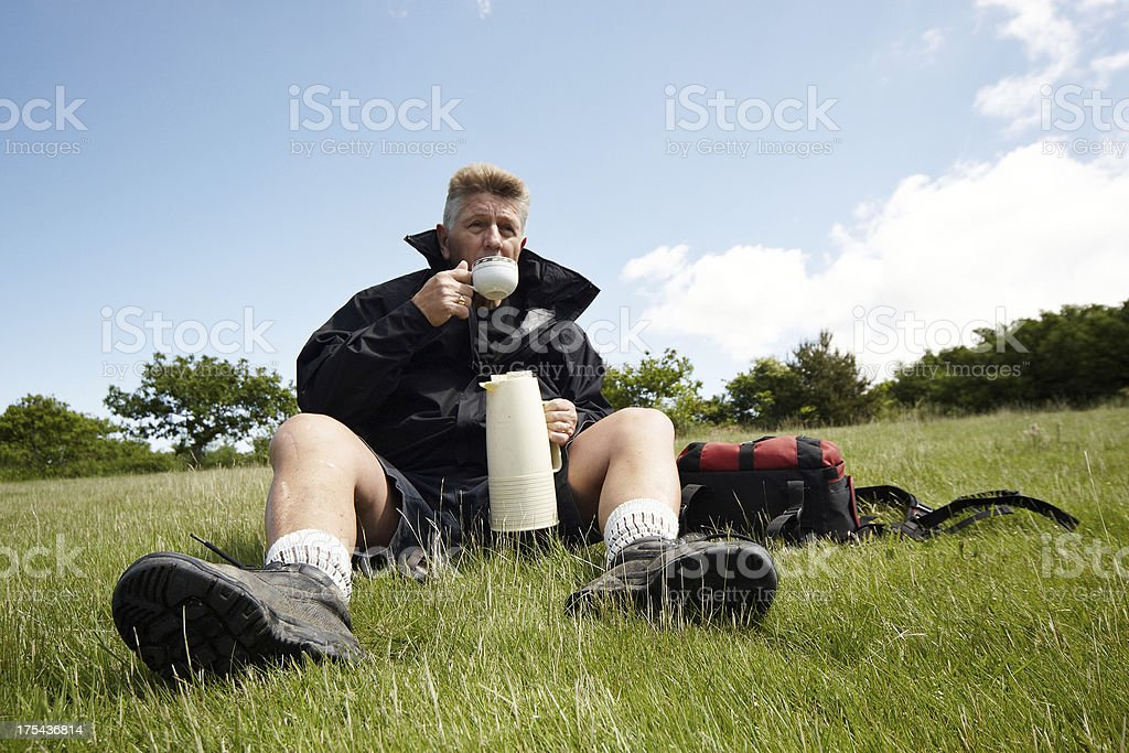 Mature male hiker taking coffee break royalty-free stock photo