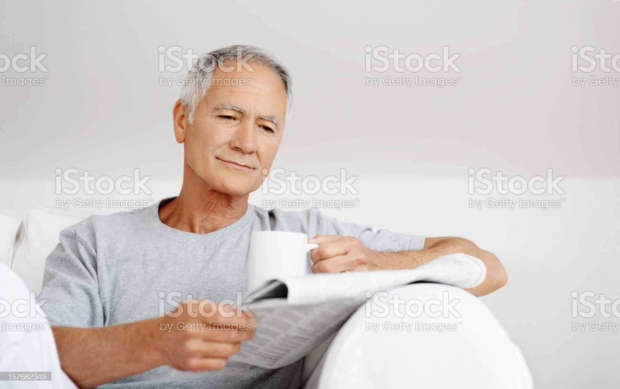 Mature male reading newspaper while holding cup of tea royalty-free stock photo