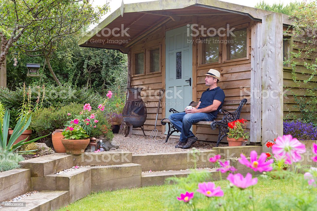 Mature Male Relaxing in His Garden stock photo