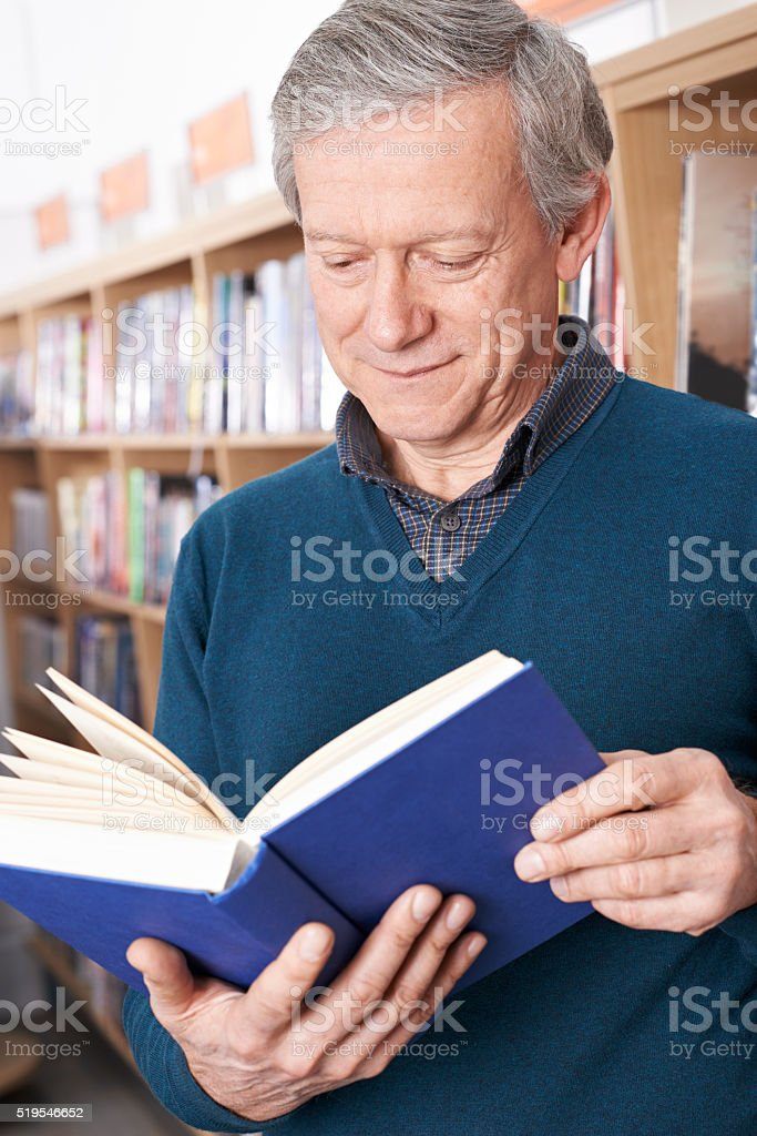 Mature Male Student Studying In Library stock photo