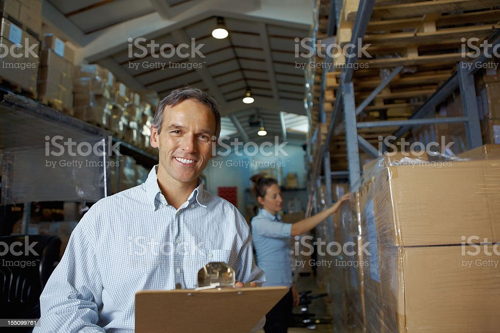 Mature male supervisor at warehouse with colleague royalty-free stock photo