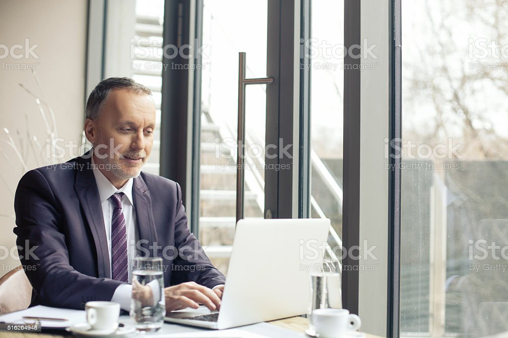 Mature male worker is using a laptop stock photo