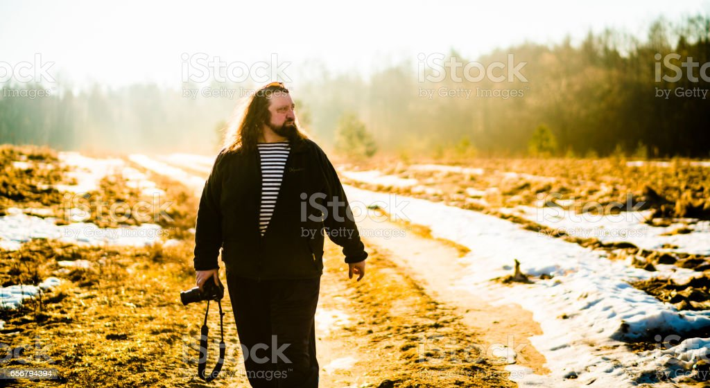 Mature man, 50 years old Caucasian with the beard and long hairs, photographer, shooting rural landscapes in Belarus stock photo