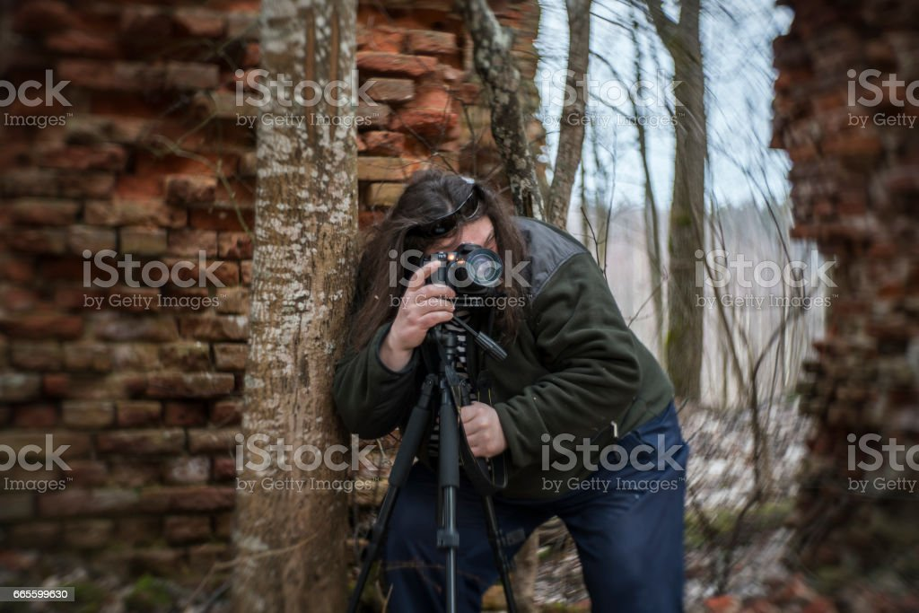 Mature man, 50 years old Caucasian with the beard and long hairs, photographer, shooting abandoned resort in Belarus stock photo