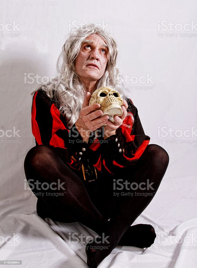 Mature man acting out Hamlet role stock photo