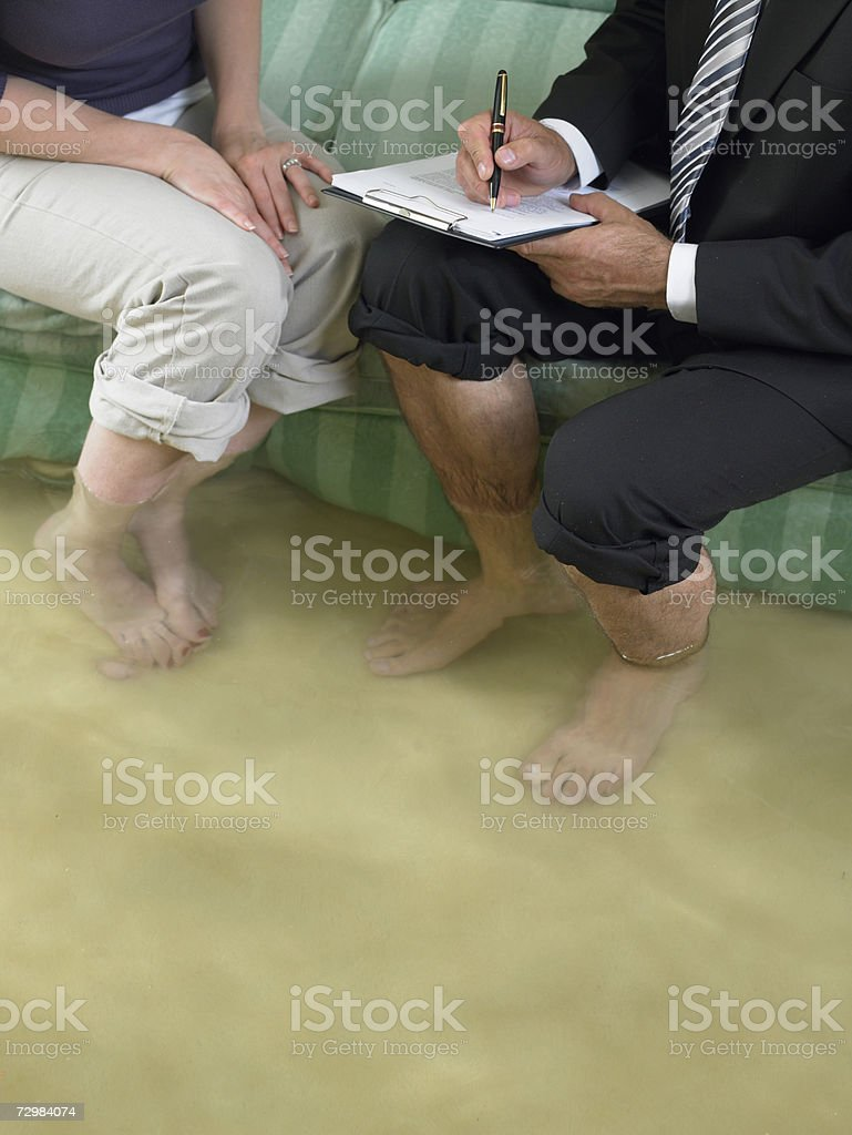 Mature man and mid adult woman sitting on sofa with water over their ankles royalty-free stock photo