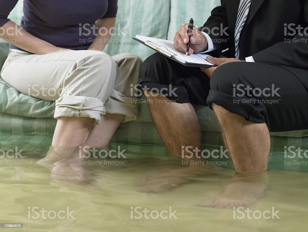 Mature man and mid adult woman sitting on sofa with water over their ankles, low section royalty-free stock photo