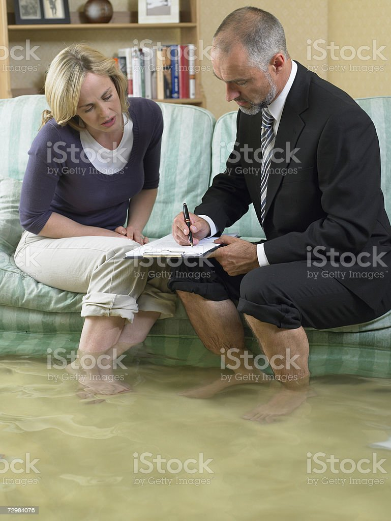 Mature man and mid adult woman sitting on sofa with water over their ankles stock photo