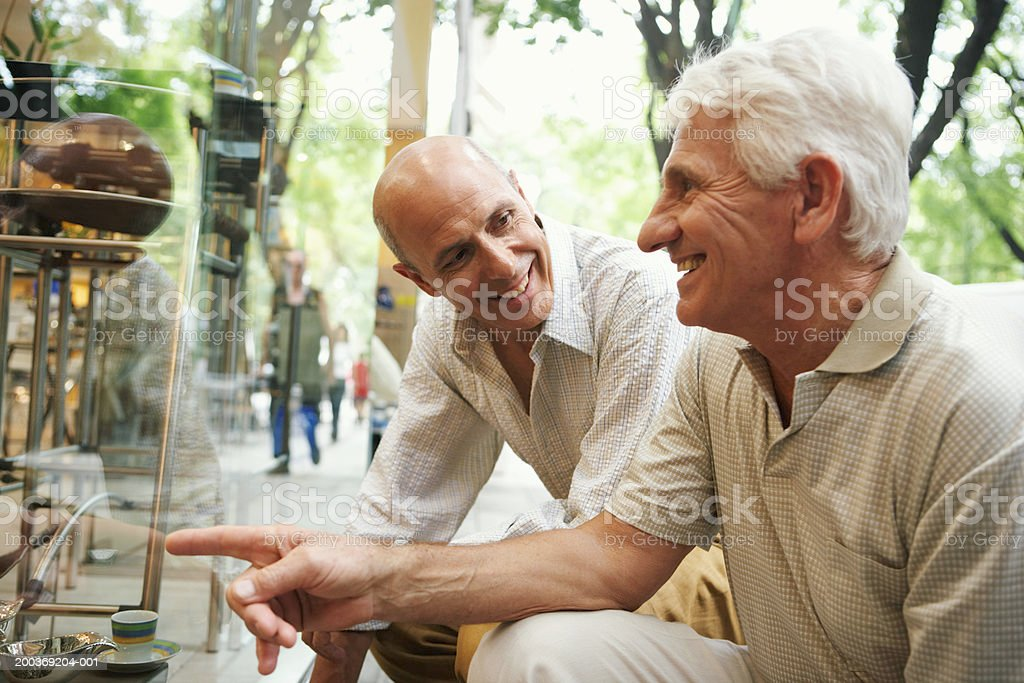 Mature man and senior man kneeling by shop window, smiling stock photo