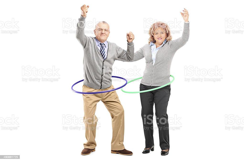 Mature man and woman exercising with hula hoop stock photo