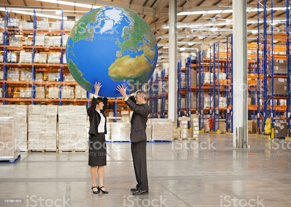 Mature man and woman holding large ball on head in warehouse royalty-free stock photo