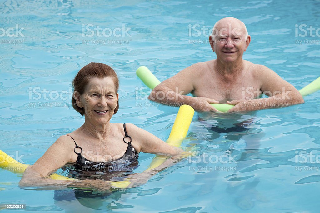 Mature man and woman in pool with pool noodles royalty-free stock photo