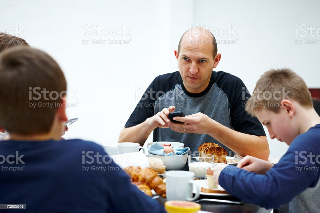 Mature man at breakfast table looking seriously at his son stock photo