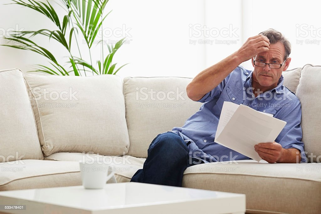 Mature man at home with bills stock photo