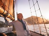 Mature man attending to ain sail and enjoying the view