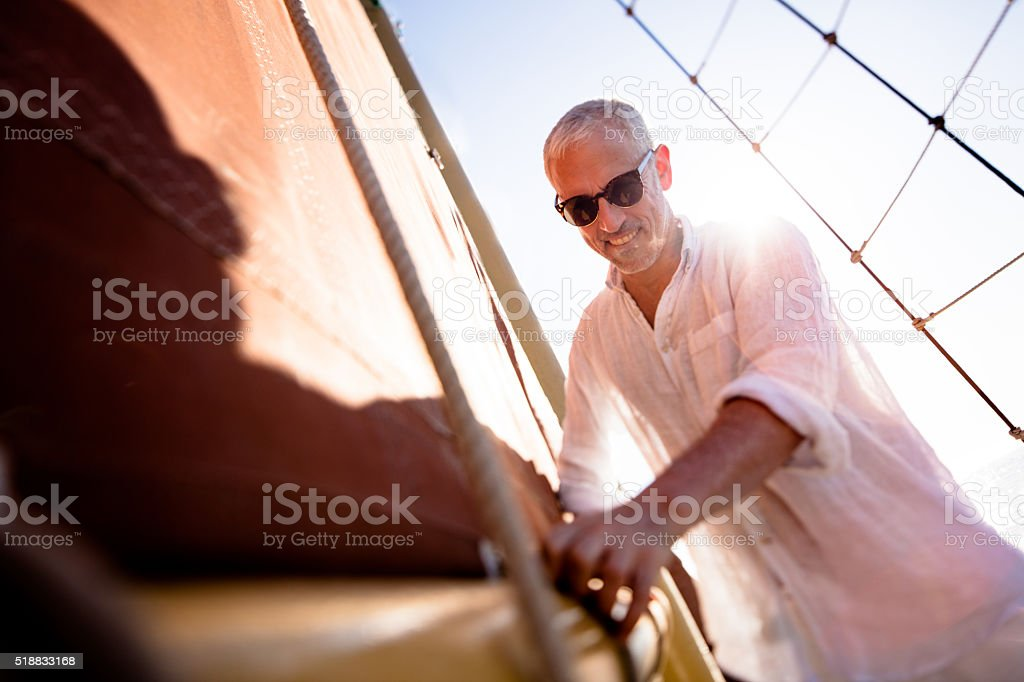 Mature man attending to the main sail on his yacht stock photo