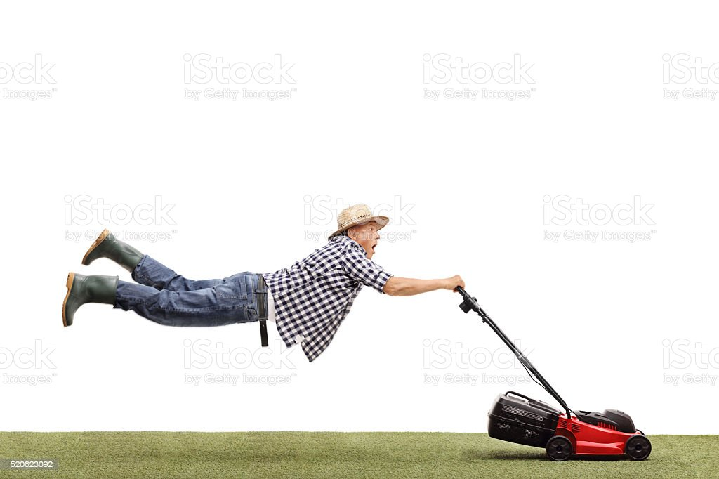 Mature man being pulled by a lawn mower stock photo