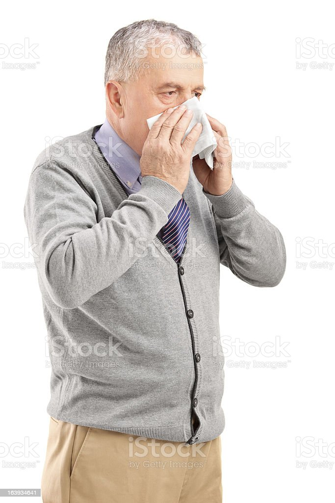 Mature man blowing his nose in a tissue royalty-free stock photo