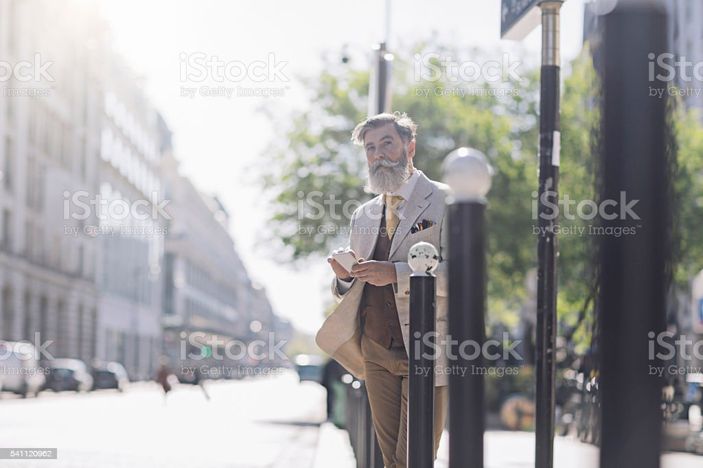 Mature man checking directions with the mobile phone in Paris stock photo