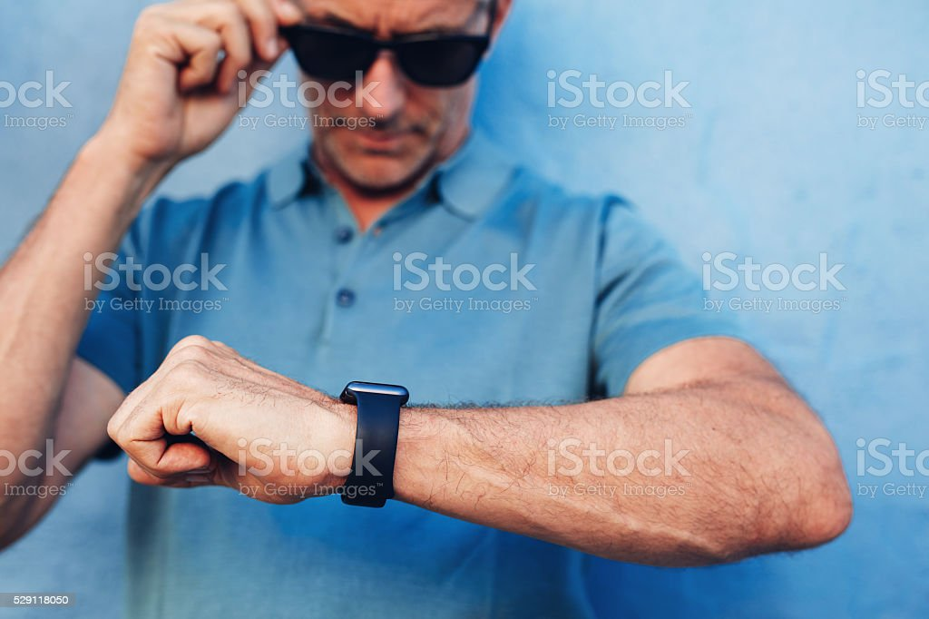 Mature man checking time on his wristwatch stock photo