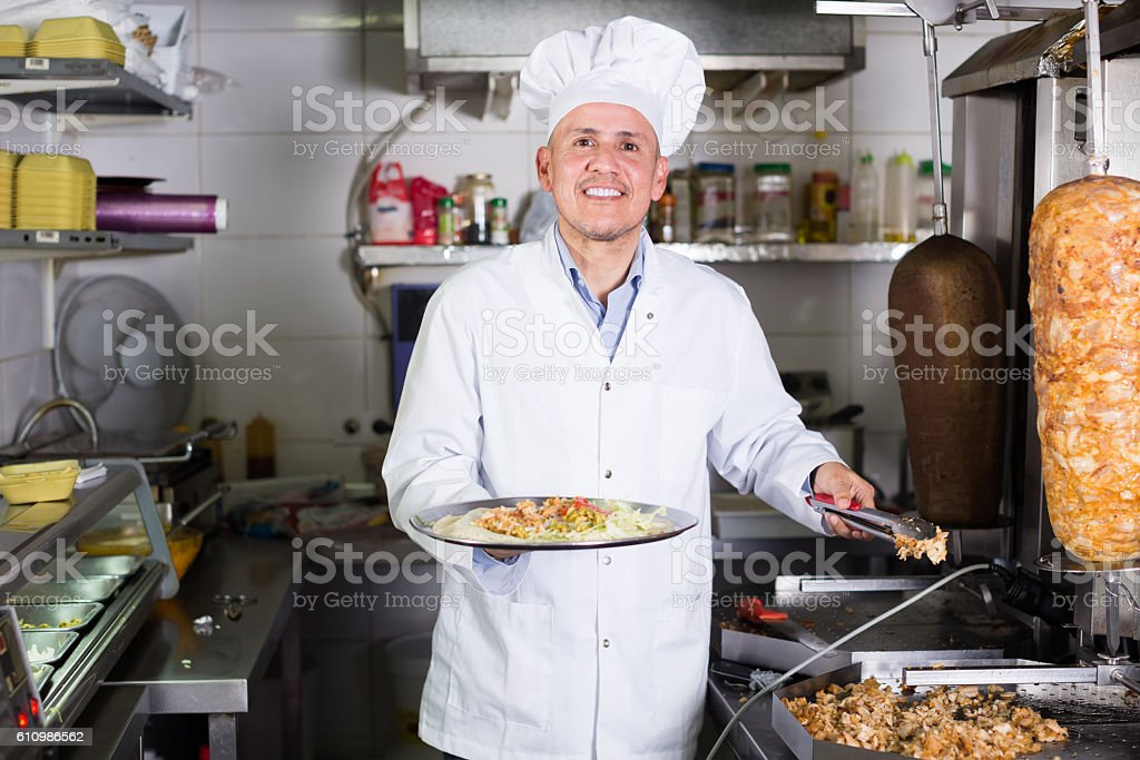 Mature man chef wearing uniform cooking kebab stock photo