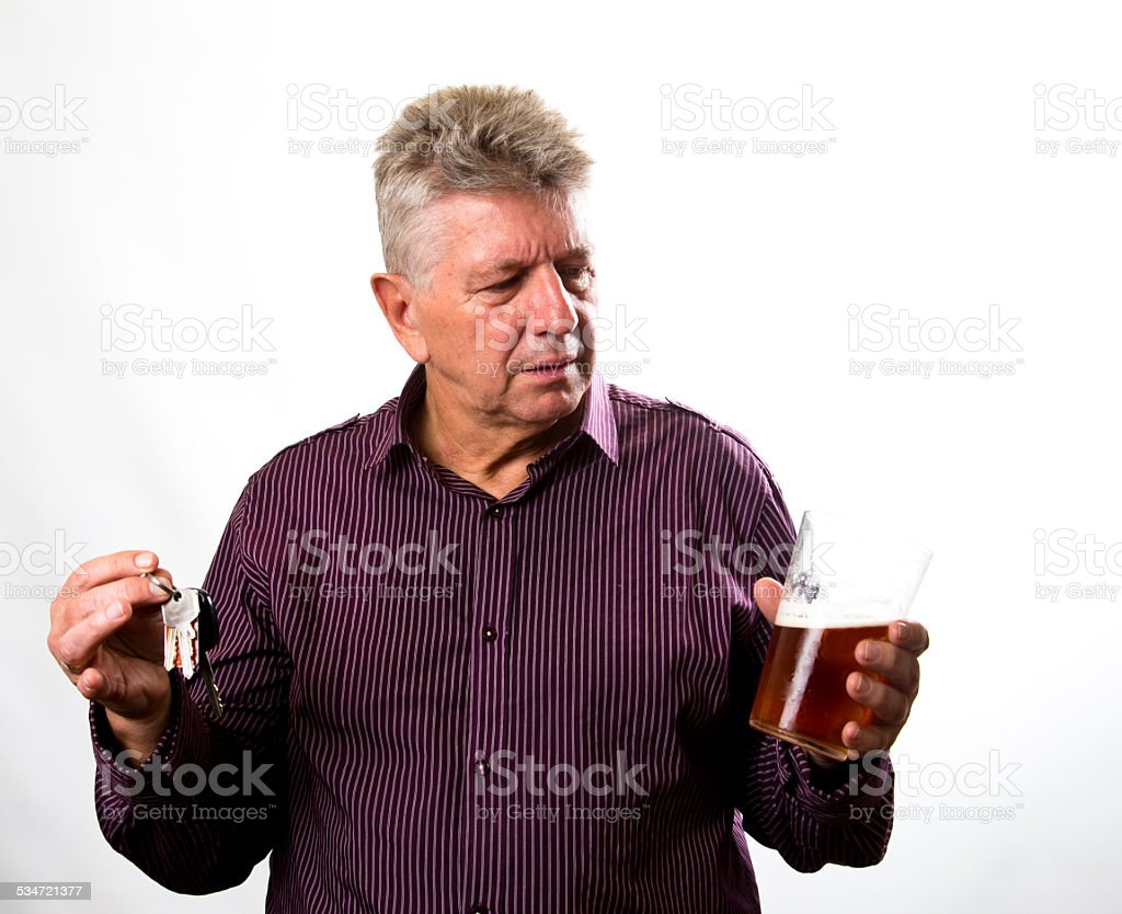 mature man choosing between drinking alcohol or driving stock photo