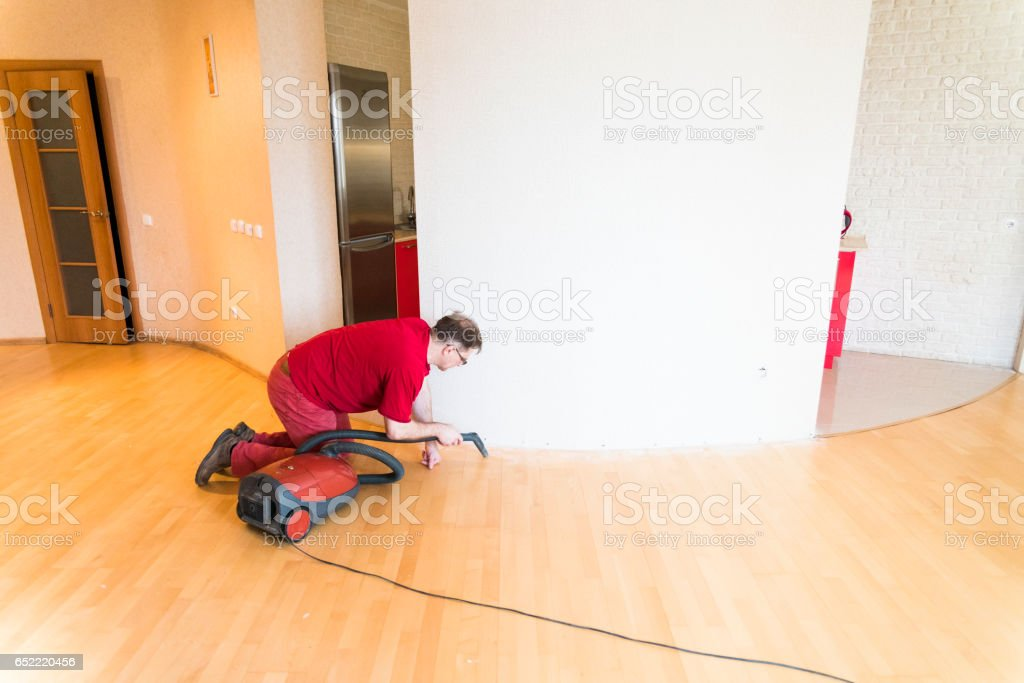 Mature man cleaning the floor with the vacuum cleaner stock photo