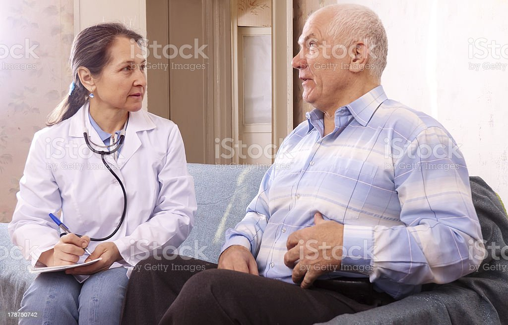 Mature man complaining  to doctor about tummy-ache stock photo