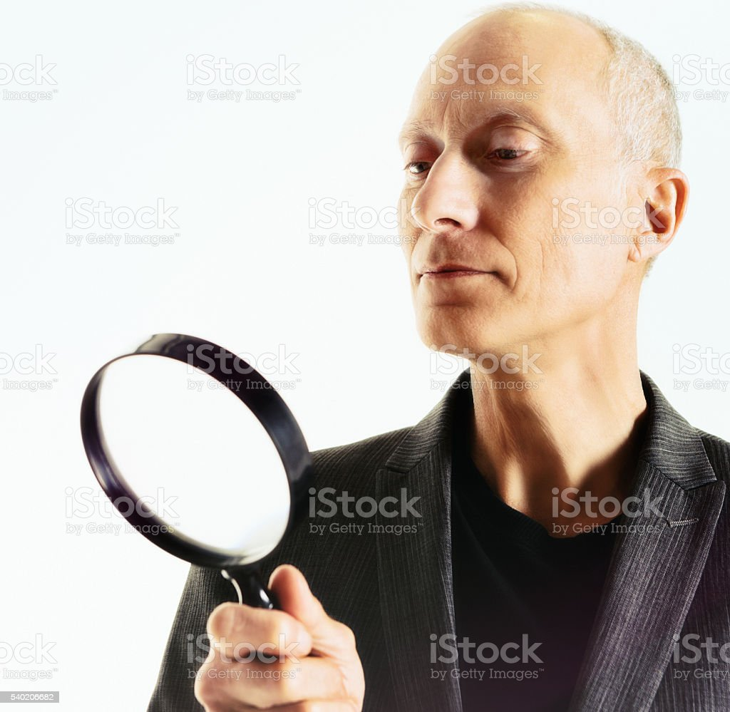 Mature man, concentrating and serious, looks through magnifying glass stock photo