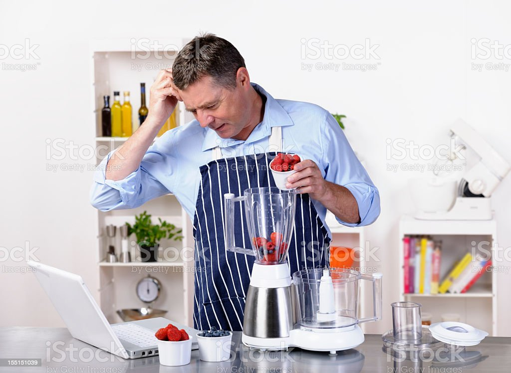 Mature Man Contemplating While Using Laptop During Meal Preparation royalty-free stock photo