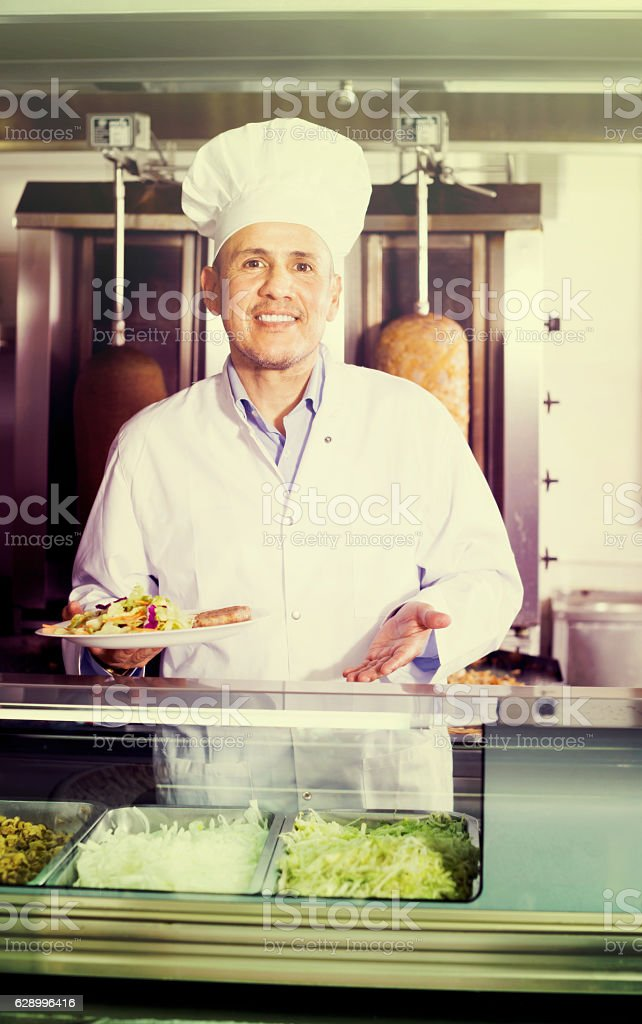 Mature man cook holding plate  in cafe stock photo