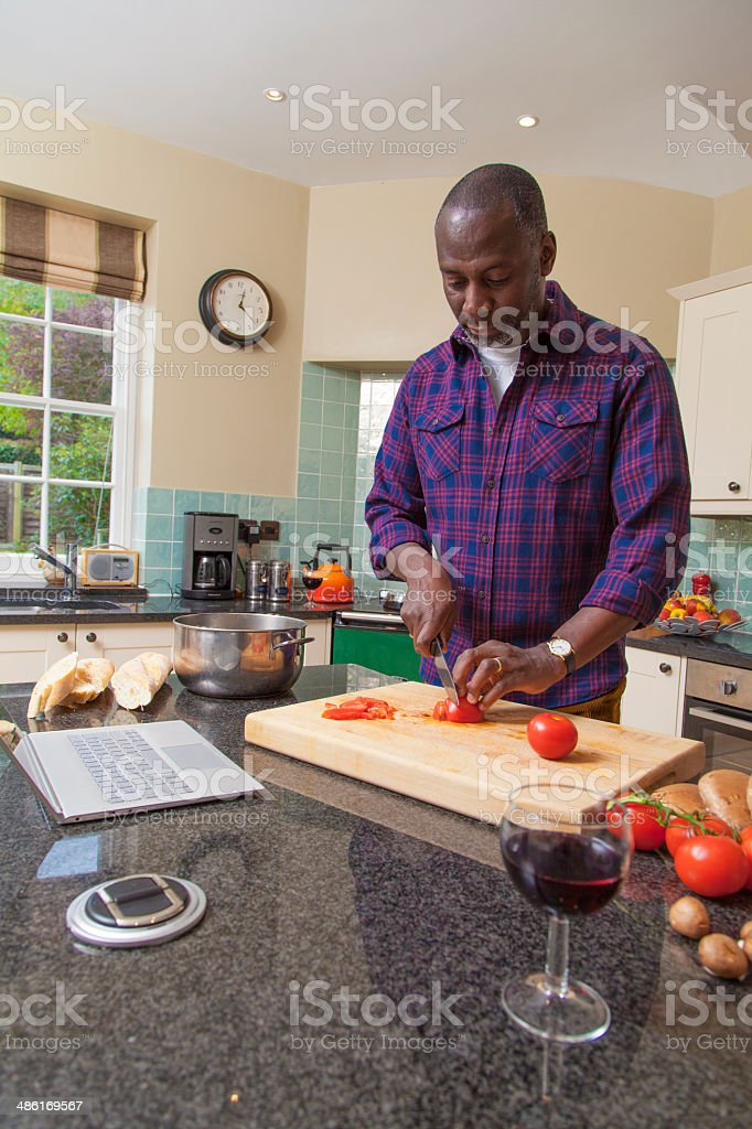 Mature man cooking in country kitchen stock photo