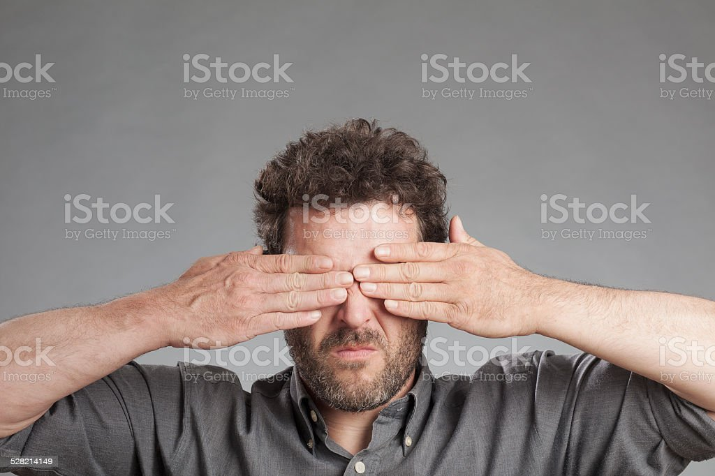 Mature man covering eyes stock photo