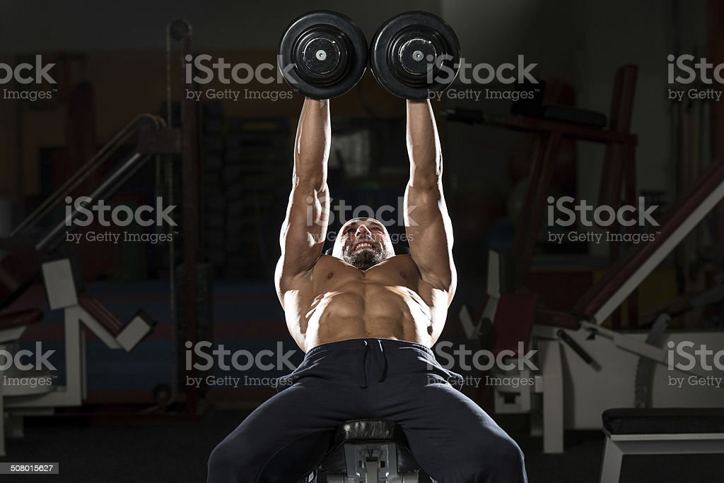 Mature Man Doing Dumbbell Incline Bench Press Workout stock photo