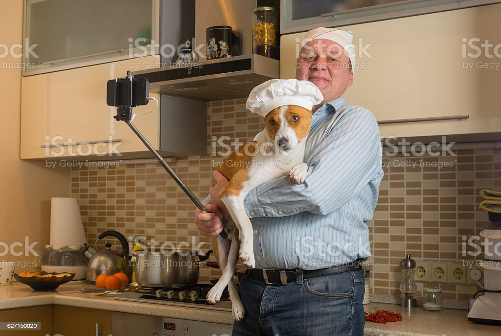 Mature man doing selfie in a kitchen with basenji dog stock photo