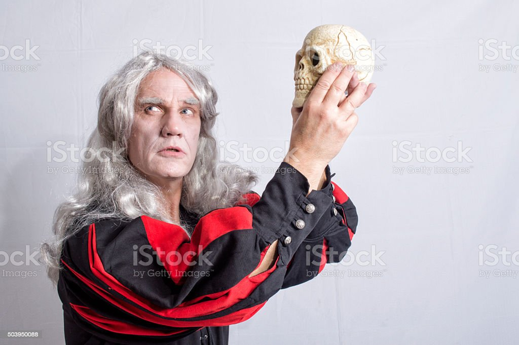 Mature man dressed as Hamlet holding a skull stock photo