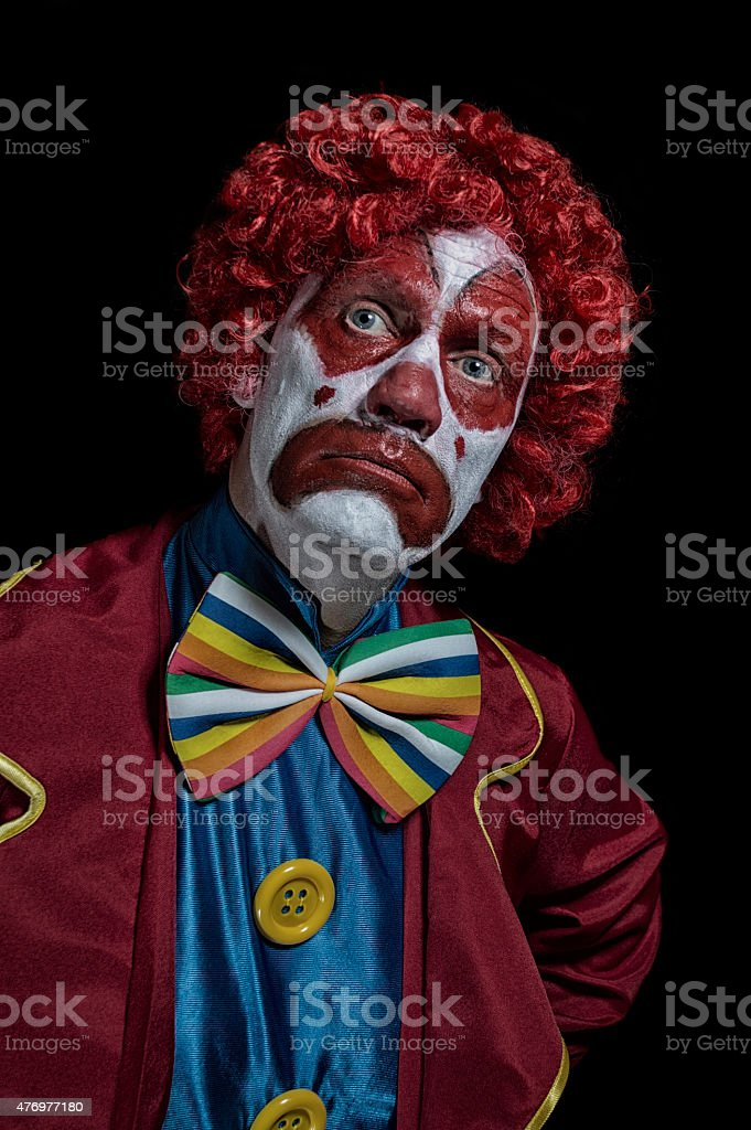 Portrait shot of a mature man dressed as a sad looking clown on a...