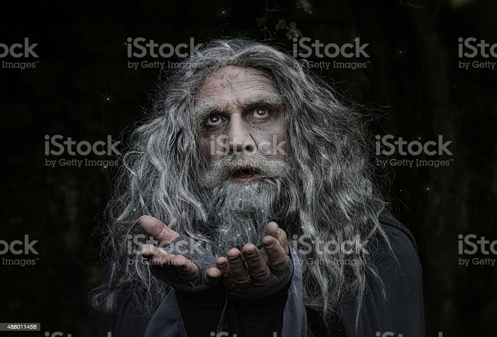 mature man dressed as wizard casting a light spell stock photo