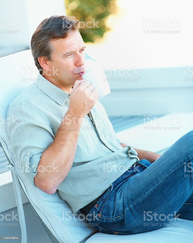 Mature man drinking coffee while relaxing on a deck chair stock photo