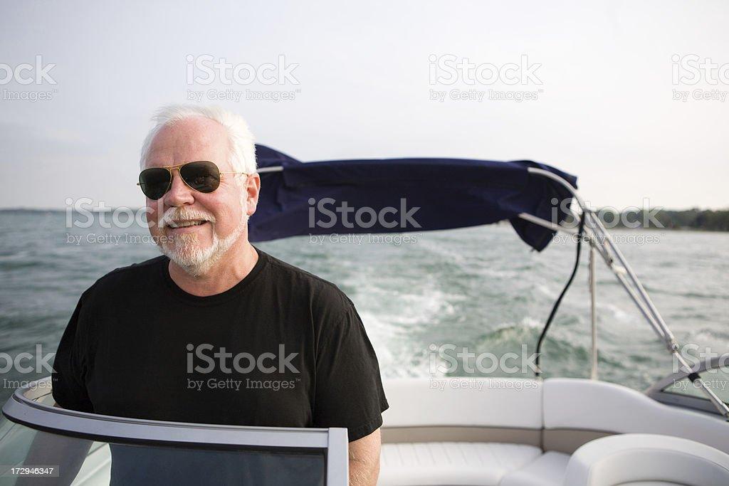 mature man driving a boat royalty-free stock photo