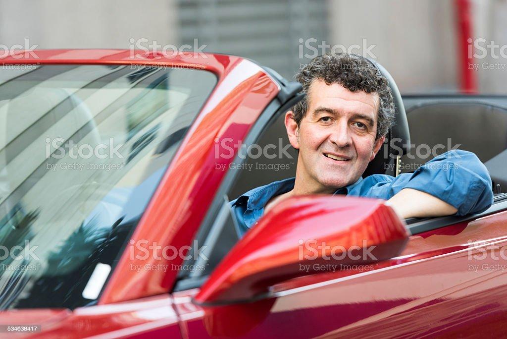 Mature man driving his convertible car stock photo