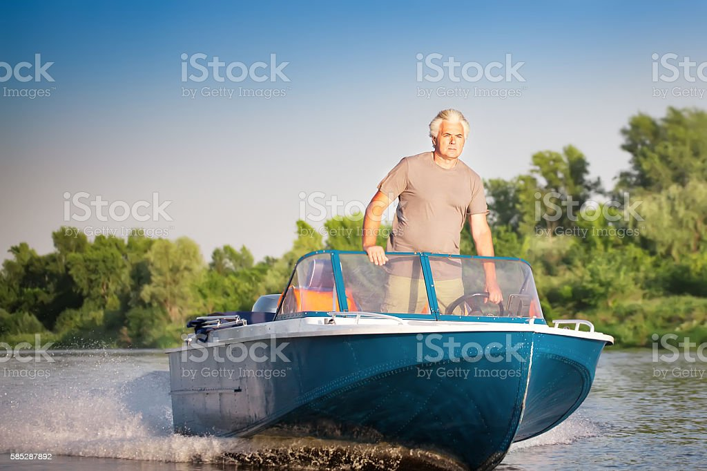Mature man driving motor boat. stock photo