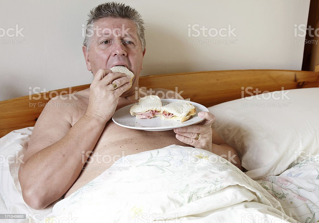 Mature man eating bacon sandwiches in bed royalty-free stock photo